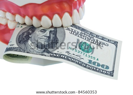 a dental model to the dentist with dollar bills. cost of health. - stock photo