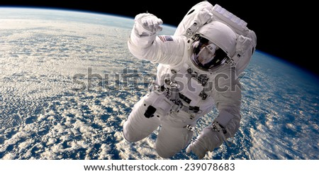 A depiction of an astronaut floating in outer space. A cloud covered Earth is below. Elements of this Image Furnished by NASA. - stock photo