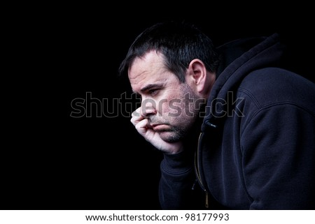 A depressed man contemplating his future, shot on black. - stock photo