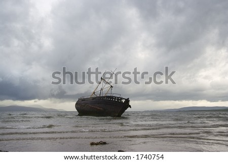 A derelict fishing boat surrounded by stormy clouds at Ettrick Bay, Bute - stock photo