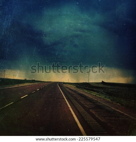 A deserted highway bordered by green fields leading to the edge of a cloudburst. - stock photo