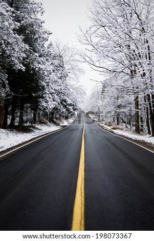 A deserted two-lane highway through a forest of snow-covered trees. - stock photo
