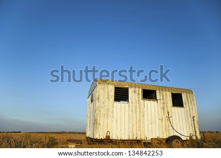 A deserted wreck of an old beaten up trailer in the middle of a harvested field in the very late hours of the afternoon. - stock photo