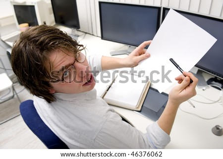 A designer asking for clarification of a document, sitting behind his desk and several computers. - stock photo