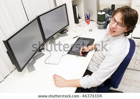 A designer at work behind two monitors, looking up at the camera - stock photo