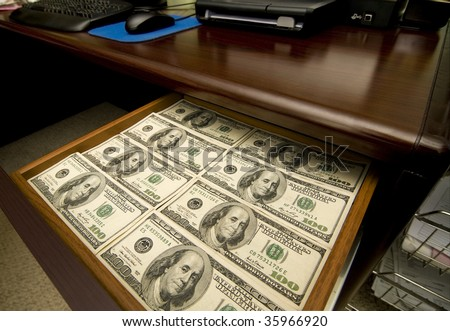 A Desk Drawer Stacked High with Hundred Dollar Bills. - stock photo