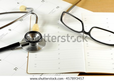 A desk top with stethoscope, address book, glasses and calendar - stock photo