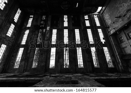 a desolate old industrial building inside, windows - stock photo