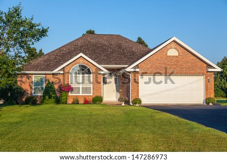 A detached brick home on a nicely landscaped lot. - stock photo