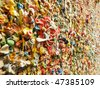 A detail view of part of the famous bubble gum wall in Post Alley near the Pike Place Market in Seattle. This landmark has built up layers of chewing gum over the years in colorful abstract pattern. - stock photo