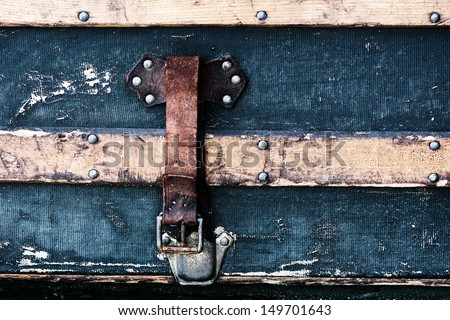 A detailed close up of the strap on an old antique luggage trunk. Focus is on the buckle.   - stock photo