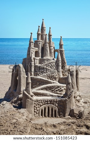A detailed, ornate sand castle with water behind. - stock photo