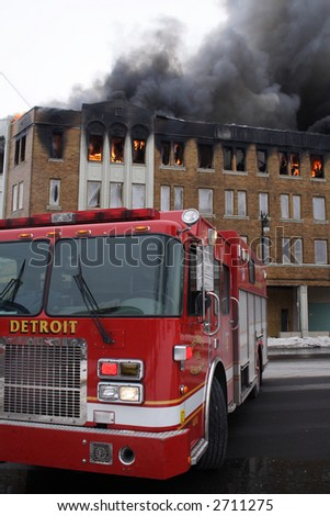 A Detroit Fire truck with a huge building fire in the background. - stock photo