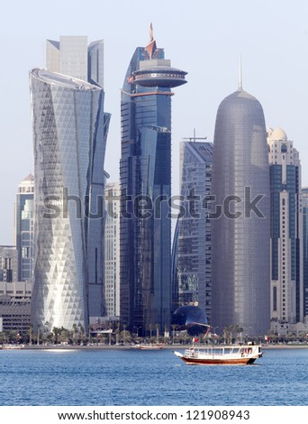 A dhow passes beneath some of the most massive buildings in Doha, Qatar, shortly before sunset in December 2012 - stock photo