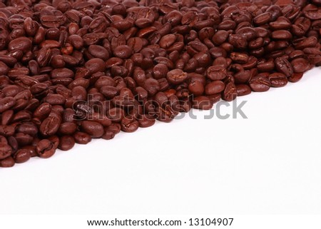 A diagonal background of coffee beans on white. - stock photo