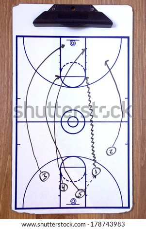 A diagram of a basketball fast break on a coach's clipboard. - stock photo