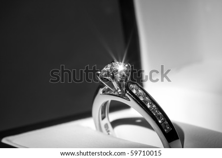 A diamond engagement ring in a box with glint/reflection. - stock photo