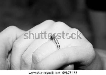 A diamond engagement ring on a lady's ring finger. - stock photo