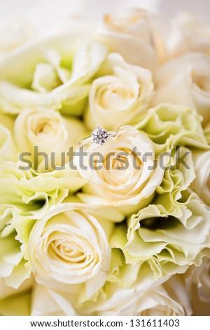 A diamond ring lies on a bouquet - stock photo