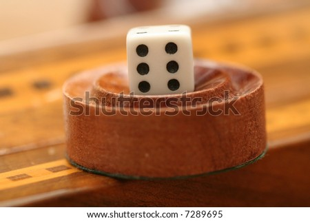a die on top of a backgammon piece - stock photo