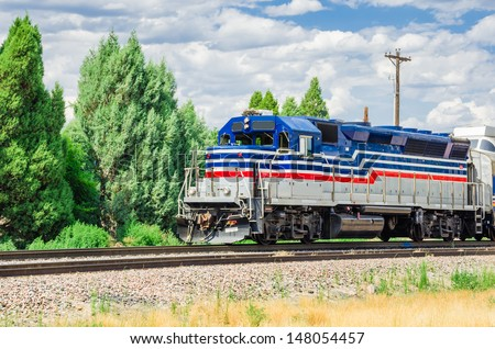 A Diesel Powered Train and Cloudy Sky - stock photo