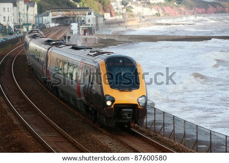 A diesel train leaves dawlish Station on the famous Brunel coastal railway - stock photo