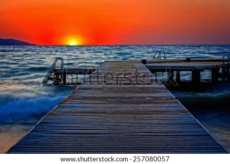 A digitally converted painting of a wooden pier at sunset - stock photo