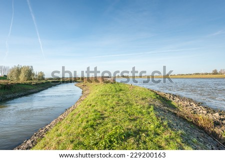 A dike, a narrow and a broad waterway on a sunny day in the fall season. - stock photo
