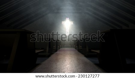 A dim old church interior lit by suns rays penetrating through a stained glass window in the shape of a crucifix reflecting colors on the floor in amongst rows of church pews - stock photo