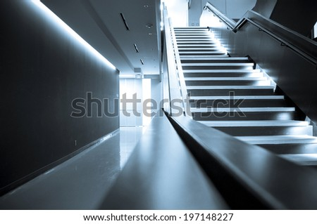 A dimly lit stairwell in an empty corridor. - stock photo