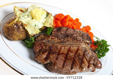A dinner of a T-bone or porterhouse steak, served with baked potato with creamed parsley potato filling and boiled carrots, garnished with English parsley - stock photo