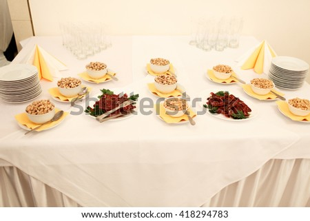 A dinner table with snacks - peanuts and meat - stock photo