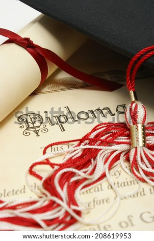 A diploma and grad hat represent a high achieving student. - stock photo