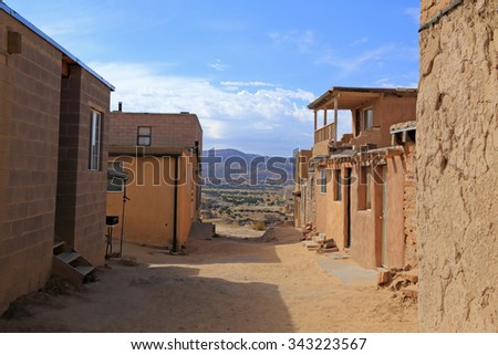 A dirt alley framed by old buildings at the Acoma Pueblo in New Mexico. - stock photo