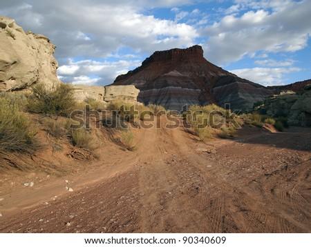 A dirt road passes through a sandy, desert wash. - stock photo