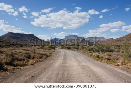 A dirt track leads invitingly into the mountains on a sunny summer's day in the Karoo, South Africa - stock photo