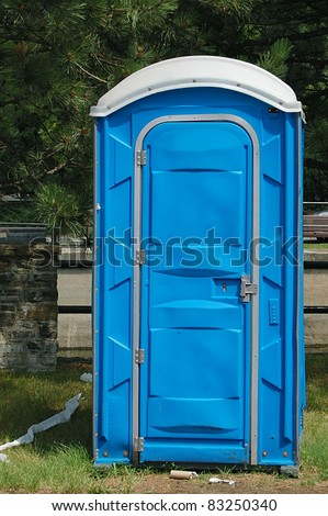 A Dirty, Blue Portable Toilet in a Park, with Scraps of Toilet paper Littering the Grass - stock photo