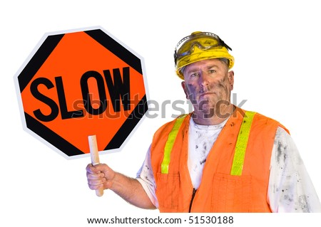 A dirty, grungy, greasy utility construction worker with hard hat, orange vest and eye protection holds up a slow sign.  Isolated on white and can be used as a design element. - stock photo