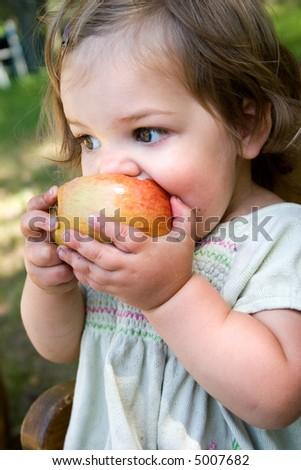 a dirty little girl eating a nice crispy apple - stock photo