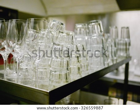 a dirty pile of dishes and glasses in a restaurant - stock photo