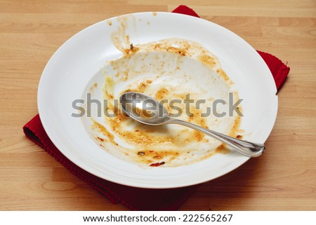 A dirty white bowl with remains of a finished dinner - stock photo