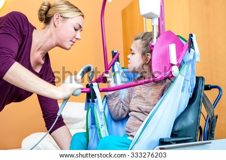 A disabled child being lifted into a wheelchair by a care assistant using special needs lifting equipment / Working with disability - stock photo