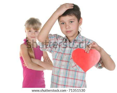 A disappointed boy is holding a red heart in his hand as his girl ignores him; isolated on the white background - stock photo