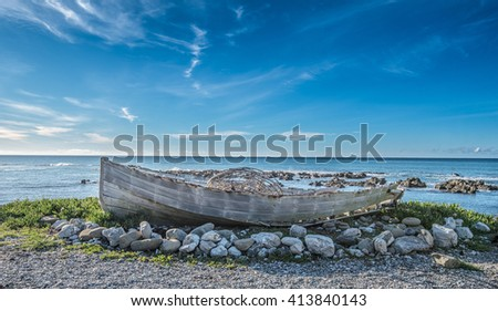 A discarded boat at beach - stock photo