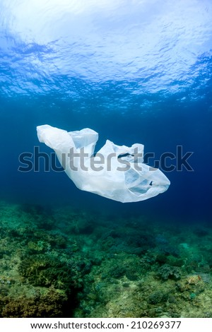 A discarded plastic garbage bag floating next to a tropical coral reef in the ocean - stock photo