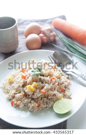 A dish of fried rice, carrot and egg on brown fabric, spoon, folk and ingredients for background - stock photo
