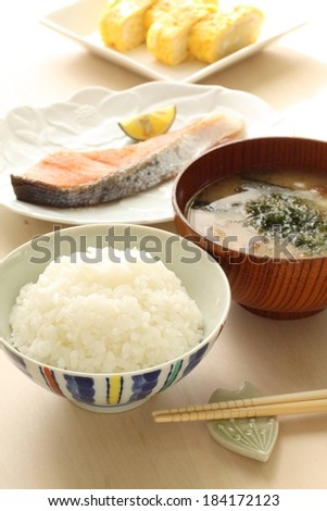 A dish of white rice, a plate of salmon and a bowl of soup. - stock photo