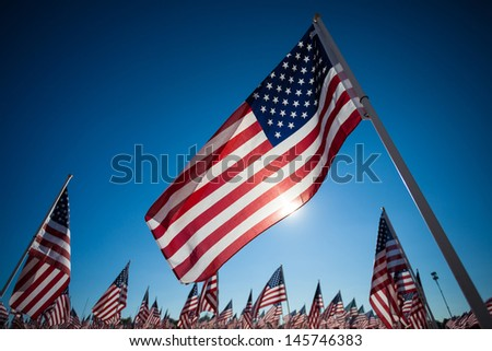A display of many American flags with a sky blue background, commemorating 9/11, memorial day, or veterans day - stock photo