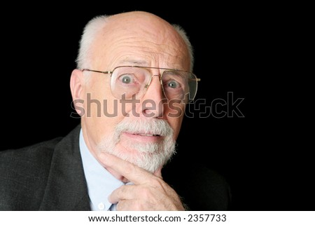 A distinguished senior man with a scared expression over a black background. - stock photo
