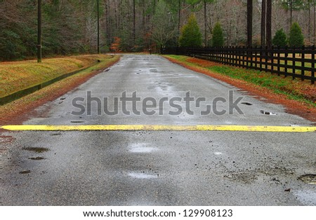 A ditch full of water runoff running along a road and fence with a speed bump and pothole in a rural neighborhood - stock photo
